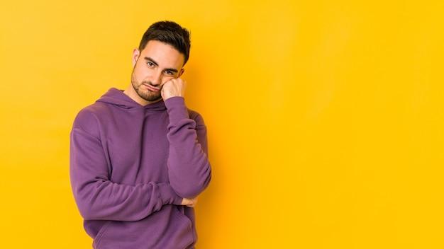 Jovem homem caucasiano isolado na parede amarela que se sente triste e pensativo, olhando para o espaço da cópia.