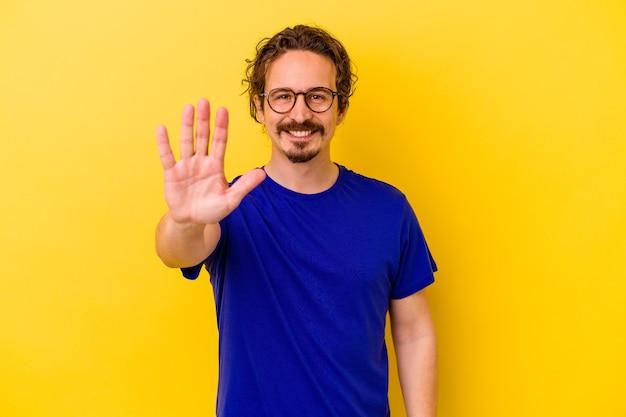 Jovem homem caucasiano isolado na parede amarela sorrindo alegre mostrando o número cinco com os dedos.