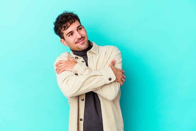 Jovem homem caucasiano isolado na parede azul abraços, sorrindo despreocupado e feliz.