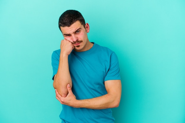 Jovem homem caucasiano isolado na parede azul cansado de uma tarefa repetitiva