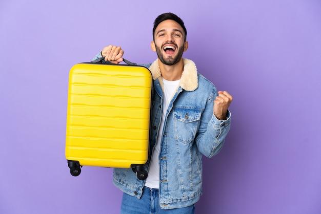 Jovem homem caucasiano isolado na parede azul de férias com mala de viagem.