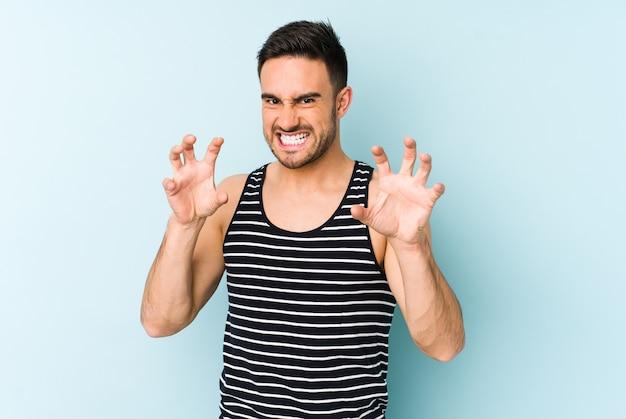 Jovem homem caucasiano isolado na parede azul, mostrando garras imitando um gato, gesto agressivo.