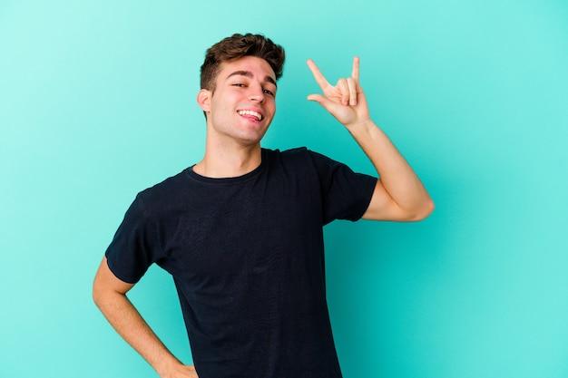 Jovem homem caucasiano isolado na parede azul, mostrando um gesto de chifres como um conceito de revolução.