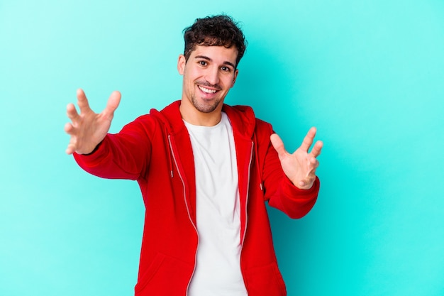 Jovem homem caucasiano isolado na parede azul se sente confiante dando um abraço na frente