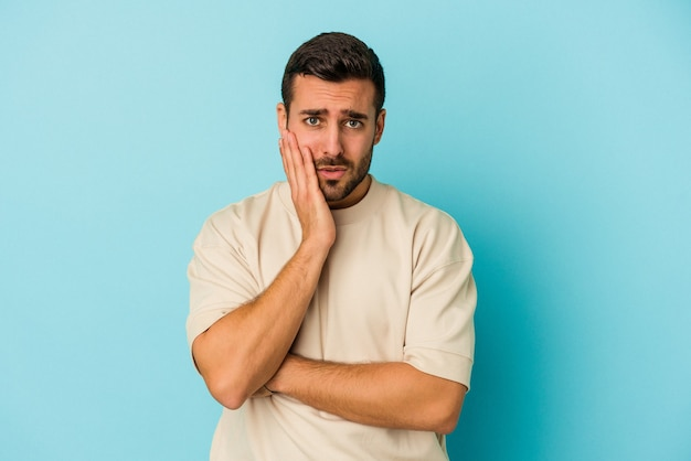 Jovem homem caucasiano isolado na parede azul sopra nas bochechas, tem uma expressão cansada. conceito de expressão facial.