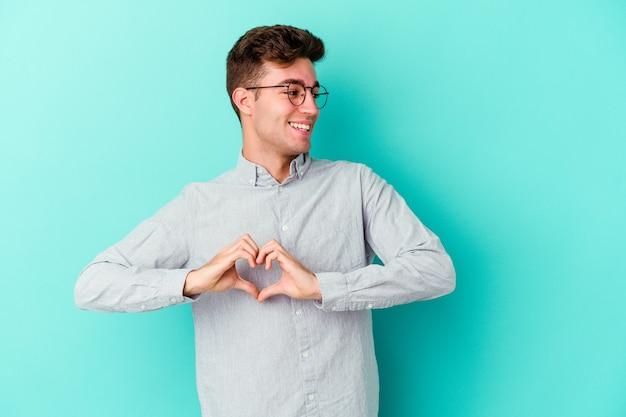 Jovem homem caucasiano isolado na parede azul, sorrindo e mostrando uma forma de coração com as mãos.