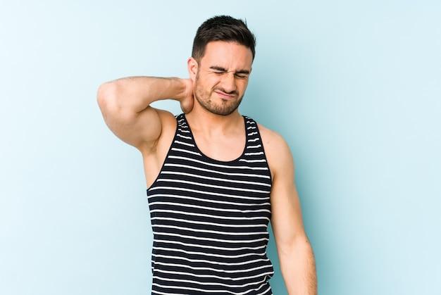 Jovem homem caucasiano isolado na parede azul, tendo uma dor no pescoço devido ao estresse, massageando e tocando com a mão.