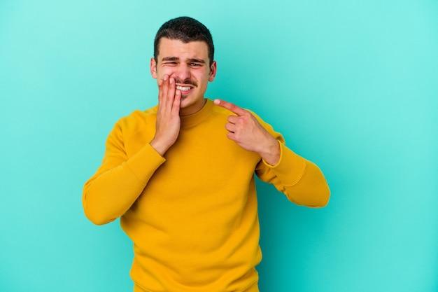 Jovem homem caucasiano isolado na parede azul, tendo uma forte dor nos dentes, dor molar.