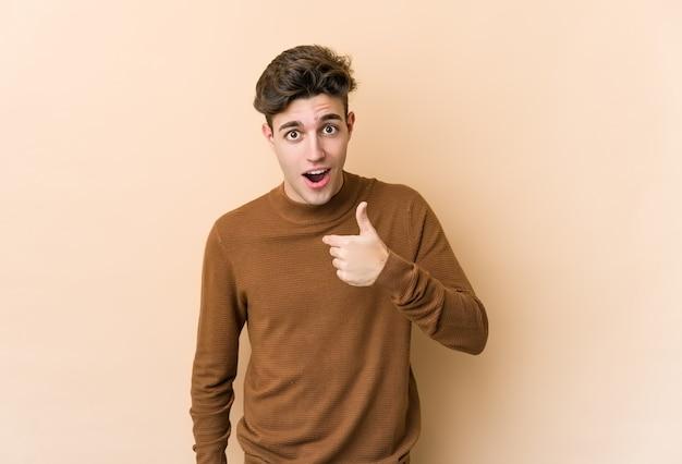 Jovem homem caucasiano isolado na parede bege surpreendeu apontando com o dedo, sorrindo amplamente.