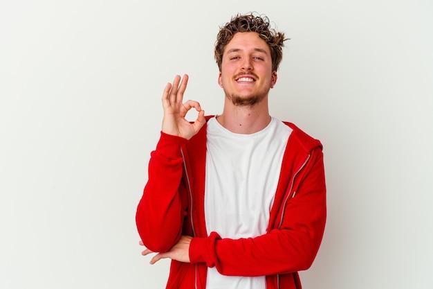 Jovem homem caucasiano isolado na parede branca pisca os olhos e faz um gesto de ok com a mão