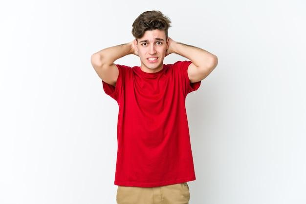 Jovem homem caucasiano isolado na parede branca, tocando a nuca, pensando e fazendo uma escolha.
