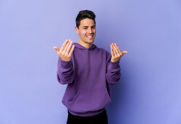 Jovem homem caucasiano isolado na parede roxa, apontando com o dedo para você como se fosse um convite para se aproximar.