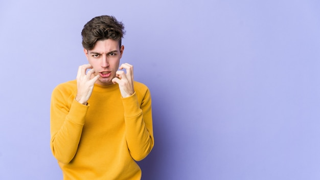 Jovem homem caucasiano isolado na parede roxa chateado gritando com as mãos tensas.