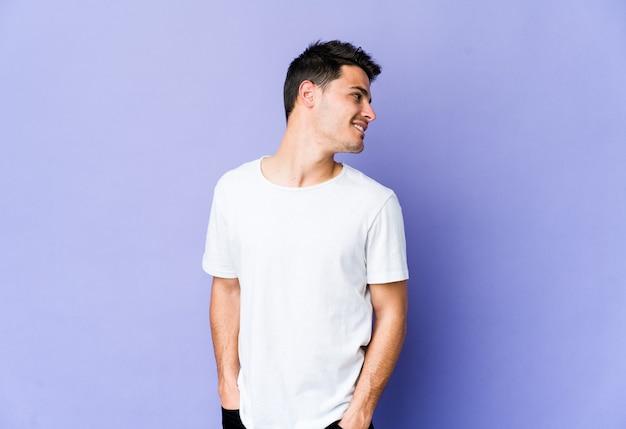 Jovem homem caucasiano isolado na parede roxa parece de lado sorrindo, alegre e agradável.