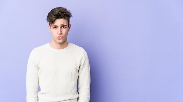 Jovem homem caucasiano isolado na parede roxa sopra nas bochechas, tem uma expressão cansada. conceito de expressão facial.