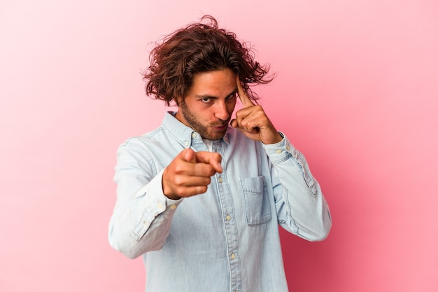 Jovem homem caucasiano isolado na rosa bakcground apontando o templo com o dedo, pensando, focado em uma tarefa.