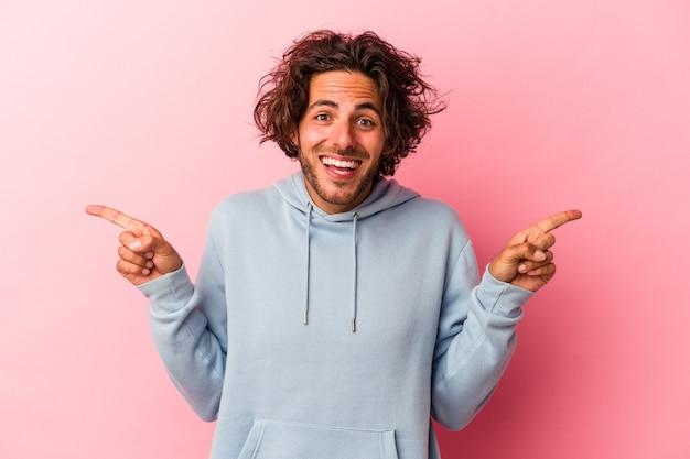 Jovem homem caucasiano isolado na rosa bakcground apontando para diferentes espaços de cópia, escolhendo um deles, mostrando com o dedo.