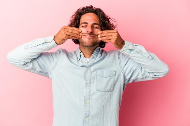 Jovem homem caucasiano isolado na rosa bakcground duvidando entre duas opções.