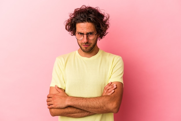 Jovem homem caucasiano isolado na rosa bakcground infeliz olhando na câmera com expressão sarcástica.
