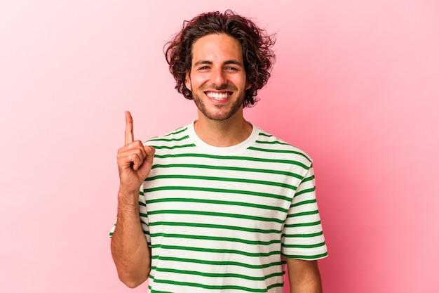 Jovem homem caucasiano isolado na rosa bakcground mostrando o número um com o dedo.
