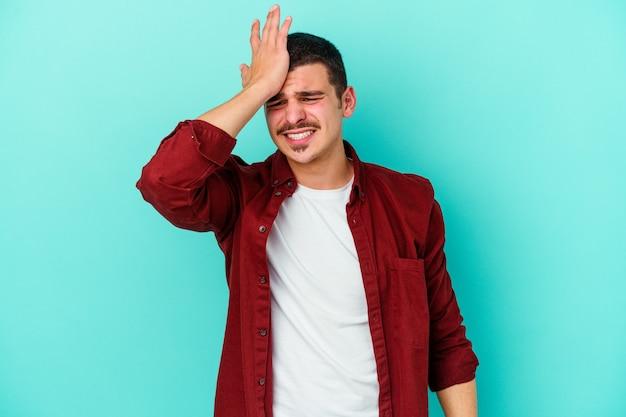 Jovem homem caucasiano isolado no azul, esquecendo de algo, batendo na testa com a palma da mão e fechando os olhos.