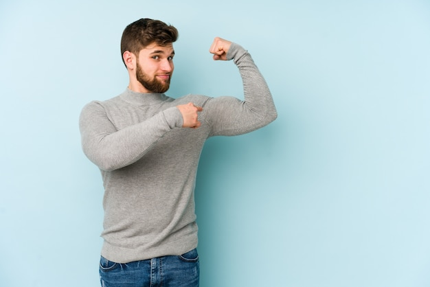 Jovem homem caucasiano isolado no azul, mostrando o gesto de força com os braços, símbolo do poder feminino