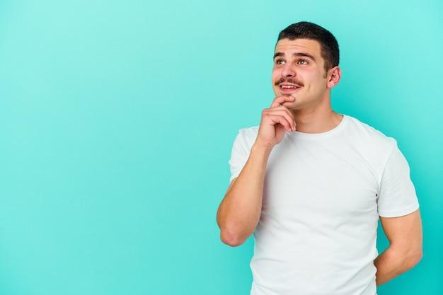 Jovem homem caucasiano isolado no azul relaxado pensando em algo olhando para um espaço de cópia.
