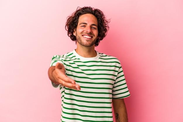 Jovem homem caucasiano isolado no bakcground rosa, esticando a mão para a câmera em um gesto de saudação.