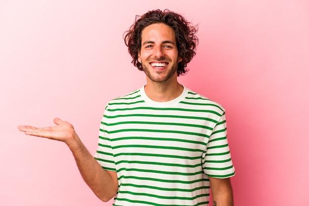 Jovem homem caucasiano isolado no bakcground rosa, mostrando um espaço de cópia na palma da mão e segurando a outra mão na cintura.