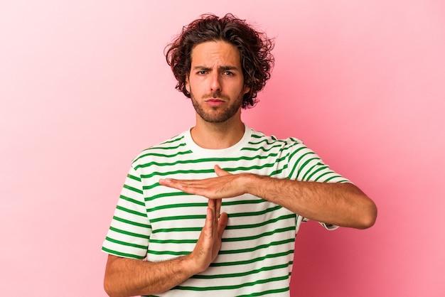 Jovem homem caucasiano isolado no bakcground rosa, mostrando um gesto de tempo limite.
