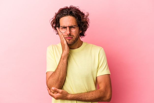 Jovem homem caucasiano isolado no bakcground rosa que está entediado, cansado e precisa de um dia de relaxamento.