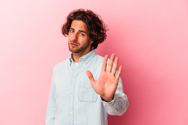 Jovem homem caucasiano isolado no bakcground rosa rejeitando alguém mostrando um gesto de nojo.