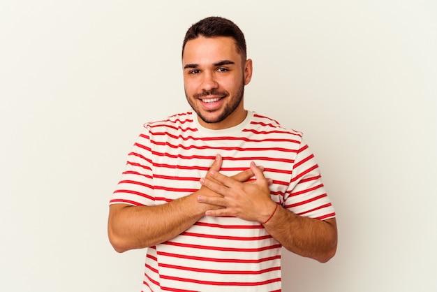 Jovem homem caucasiano isolado no branco tem uma expressão amigável, pressionando a palma da mão no peito. conceito de amor.