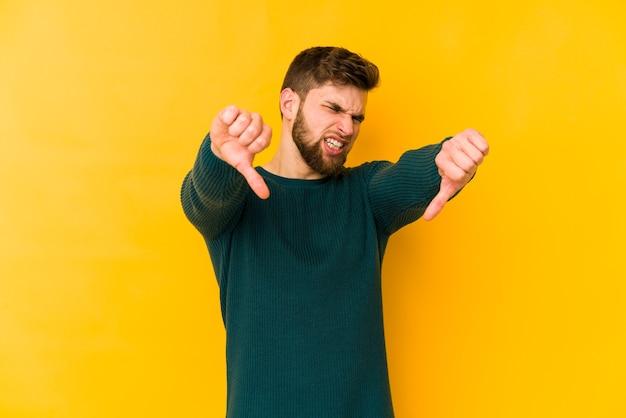 Jovem homem caucasiano isolado no espaço amarelo, mostrando o polegar para baixo e expressando antipatia.