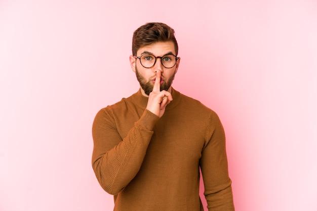 Jovem homem caucasiano isolado no espaço rosa, mantendo um segredo ou pedindo silêncio.