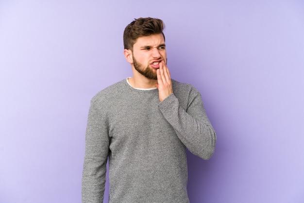 Jovem homem caucasiano isolado no espaço roxo, tendo uma forte dor nos dentes, dor molar.