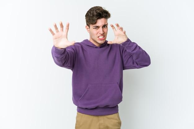 Jovem homem caucasiano isolado no fundo branco chateado gritando com as mãos tensas.