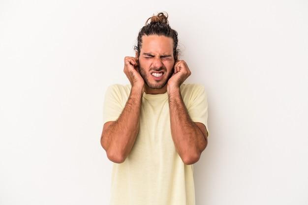 Jovem homem caucasiano isolado no fundo branco, cobrindo as orelhas com as mãos.