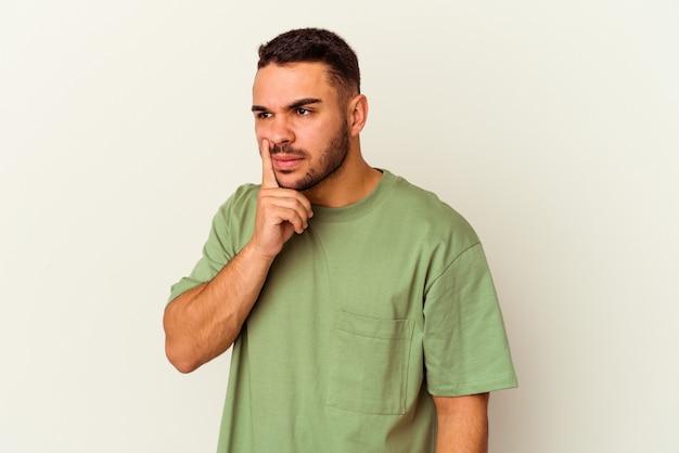 Jovem homem caucasiano isolado no fundo branco, contemplando, planejando uma estratégia, pensando na forma de um negócio.