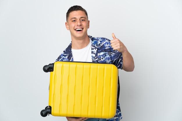 Jovem homem caucasiano isolado no fundo branco de férias com mala de viagem e com o polegar para cima