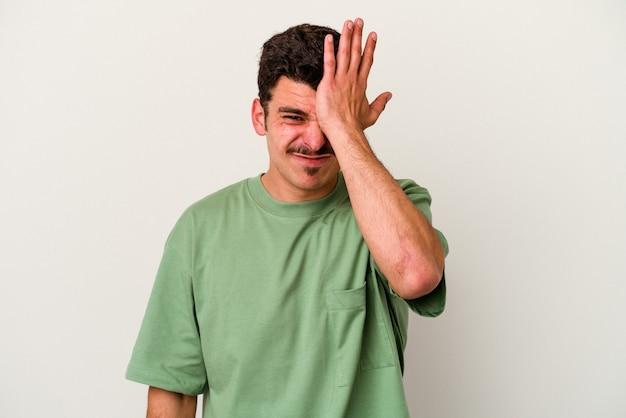 Jovem homem caucasiano isolado no fundo branco, esquecendo de algo, batendo na testa com a palma da mão e fechando os olhos.