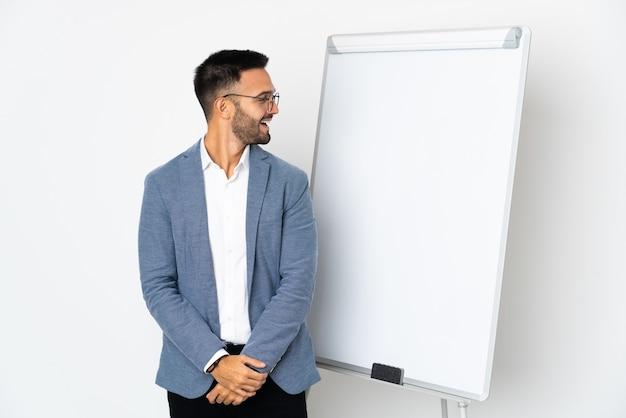 Jovem homem caucasiano isolado no fundo branco fazendo uma apresentação no quadro branco e olhando de lado