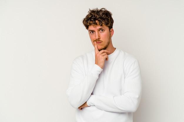 Jovem homem caucasiano isolado no fundo branco infeliz olhando na câmera com expressão sarcástica.