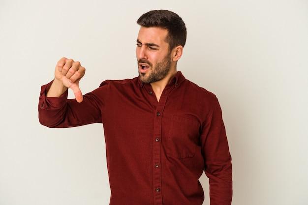 Jovem homem caucasiano isolado no fundo branco, mostrando o polegar para baixo e expressando antipatia.
