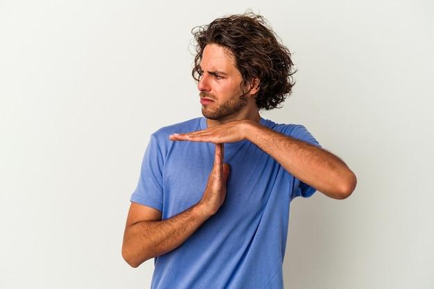 Jovem homem caucasiano isolado no fundo branco, mostrando um gesto de tempo limite.