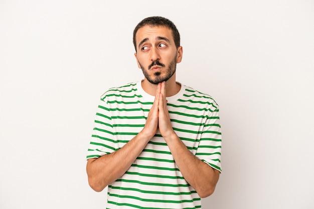 Jovem homem caucasiano isolado no fundo branco orando, mostrando devoção, pessoa religiosa em busca de inspiração divina.