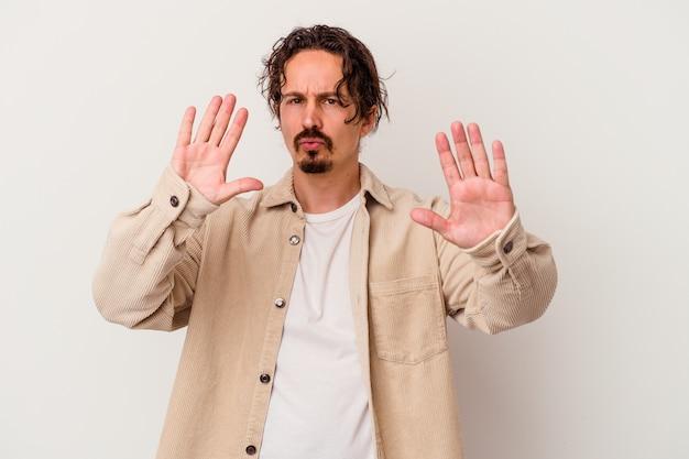Jovem homem caucasiano isolado no fundo branco, rejeitando alguém mostrando um gesto de nojo.