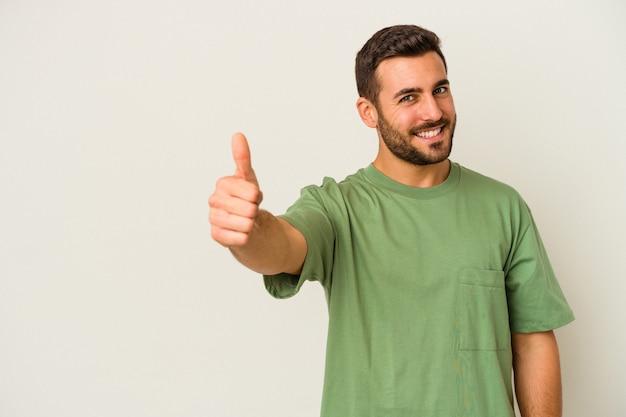 Jovem homem caucasiano isolado no fundo branco, sorrindo e levantando o polegar