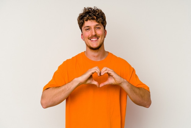 Jovem homem caucasiano isolado no fundo branco, sorrindo e mostrando uma forma de coração com as mãos.