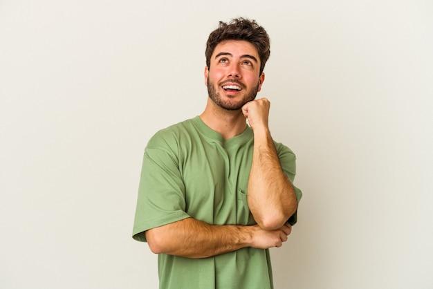 Jovem homem caucasiano isolado no fundo branco, sorrindo feliz e confiante, tocando o queixo com a mão.
